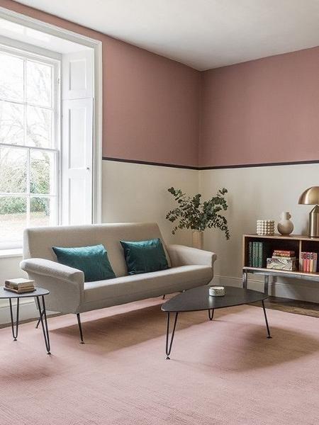 Sala de estar com técnica de pintura meia parede rosa e outra cor neutra