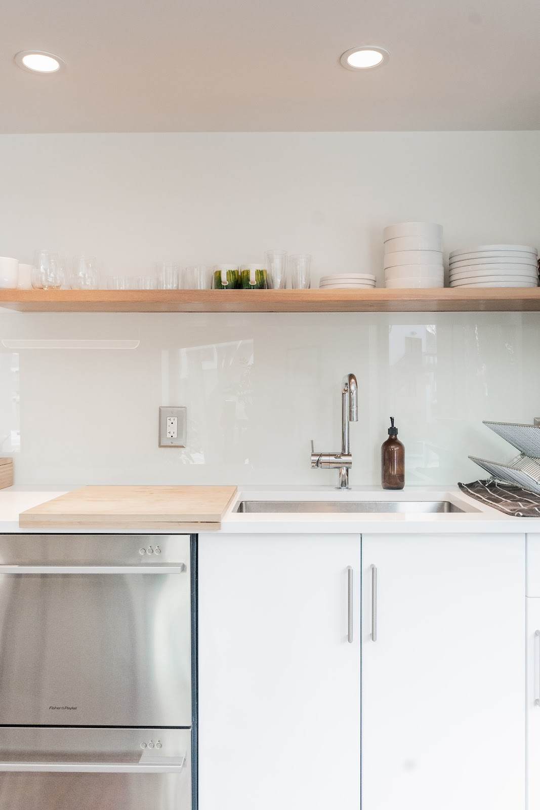 Kitchen done in white and beige tones with an open shelf stacked with plates, bowls and glasses.