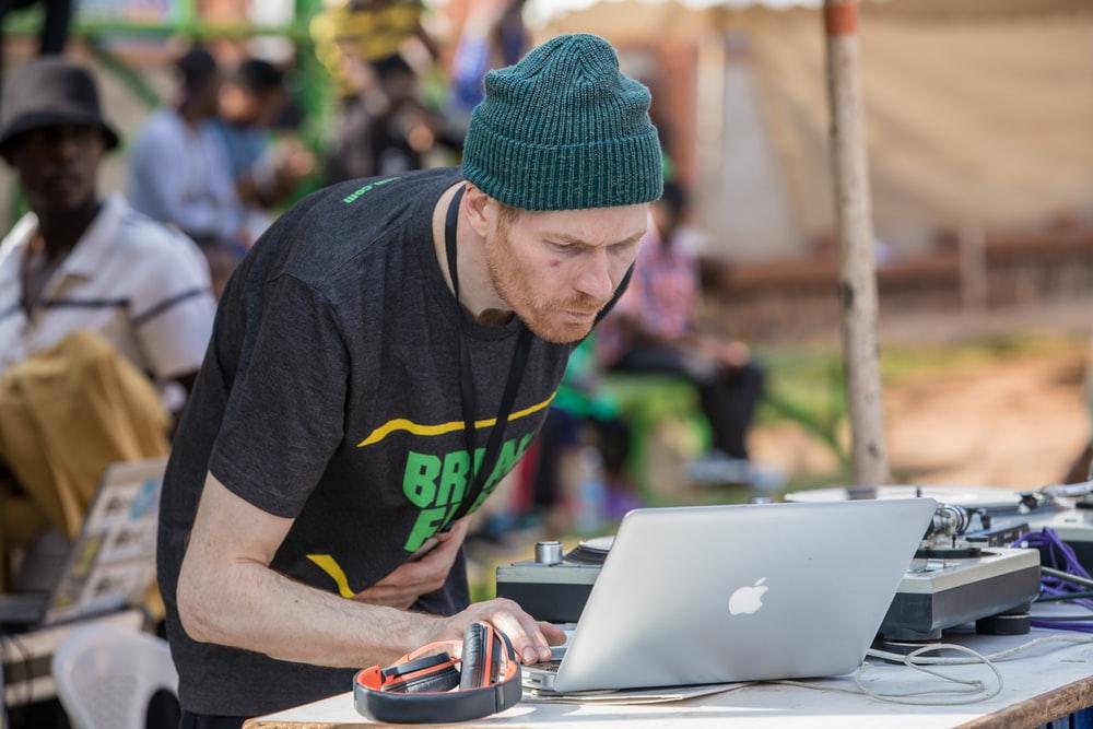 man using MacBook beside black and orange headphones
