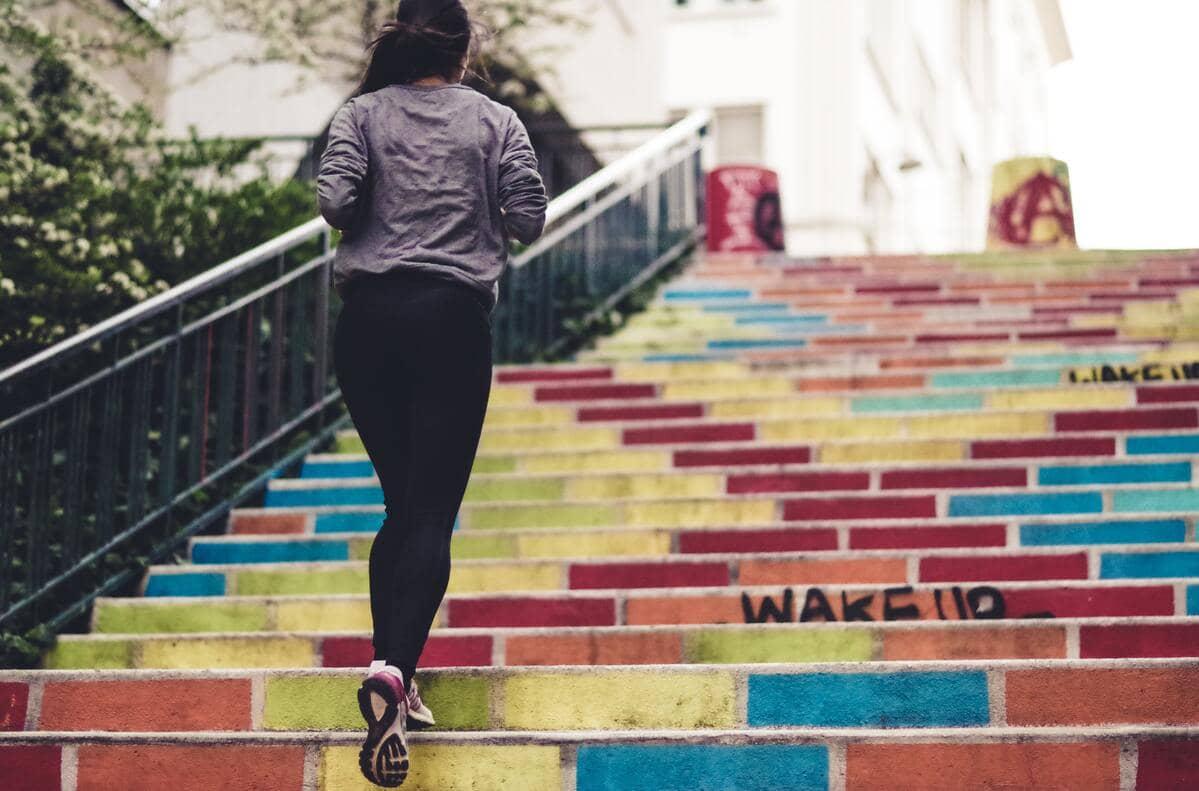 Una ragazza con un completo sportivo che corre su una scalinata colorata