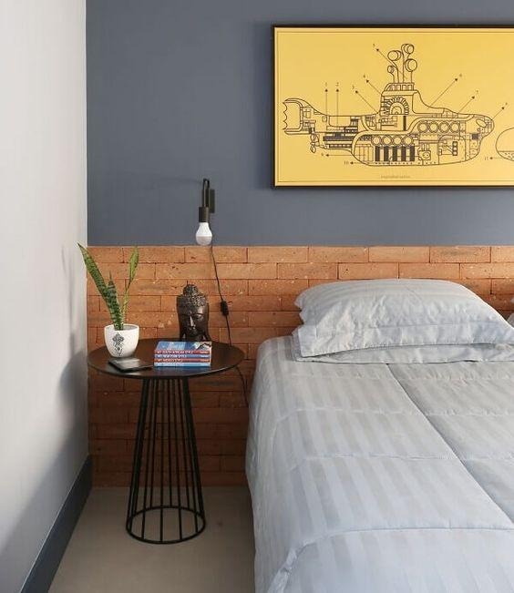 Quarto com cabeceira de tijolinhos, parede azul, mesinha de canto redonda preta e cama de casal.