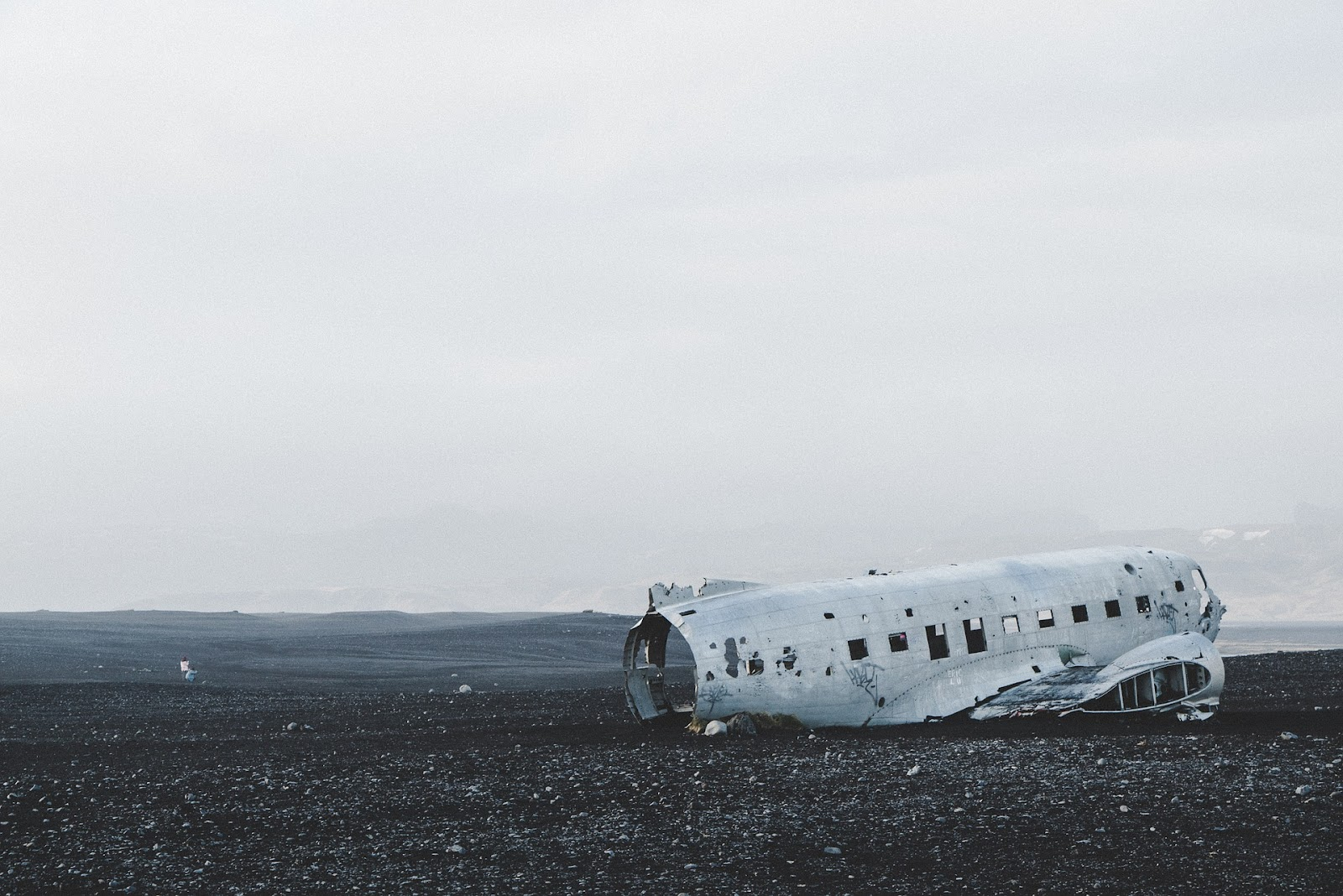 dc-3 plane wreck tourist attraction on black pebble beach seen on a misty day in iceland