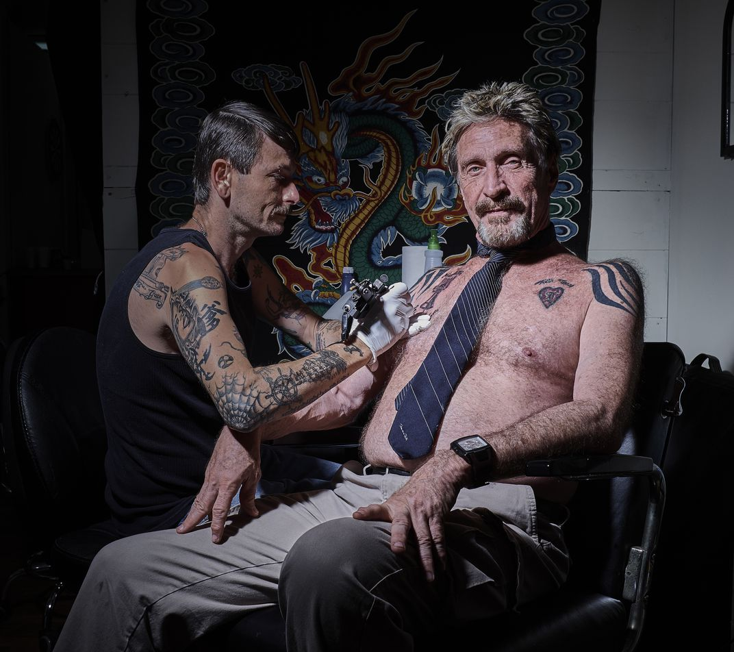 "John Mcafee, se faisant tatouer le logo de sa cryptomonnaie ""GHOST""."