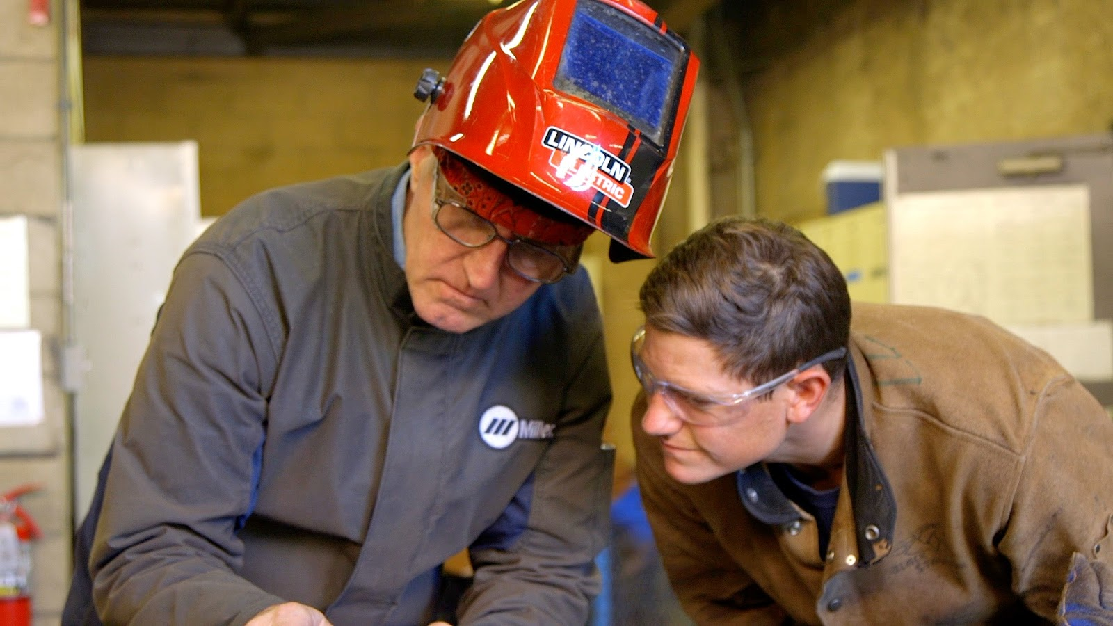 Welding instructor working with welding student