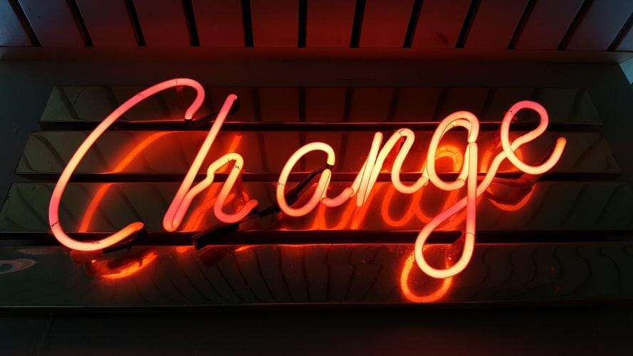 orange neon sign saying 'change'.