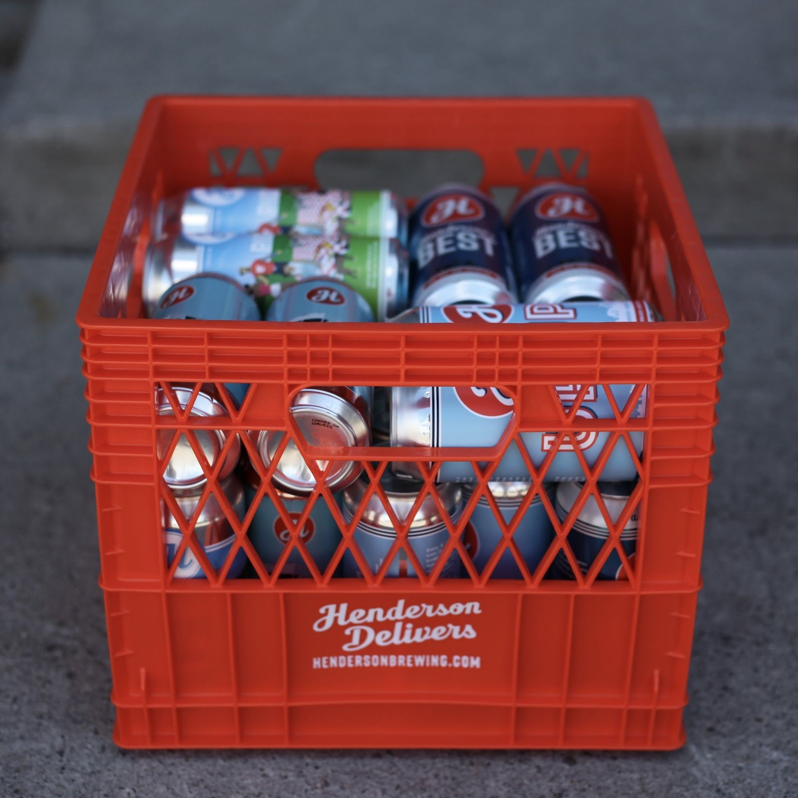 A bright orange milk crate that says 'Henderson Delivers' on it, filled with cans of delicious Henderson beer