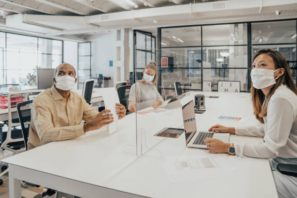 Businesspeople working at office with glass partition dividing them Businesspeople working at office with glass partition dividing them coworking space stock pictures, royalty-free photos & images
