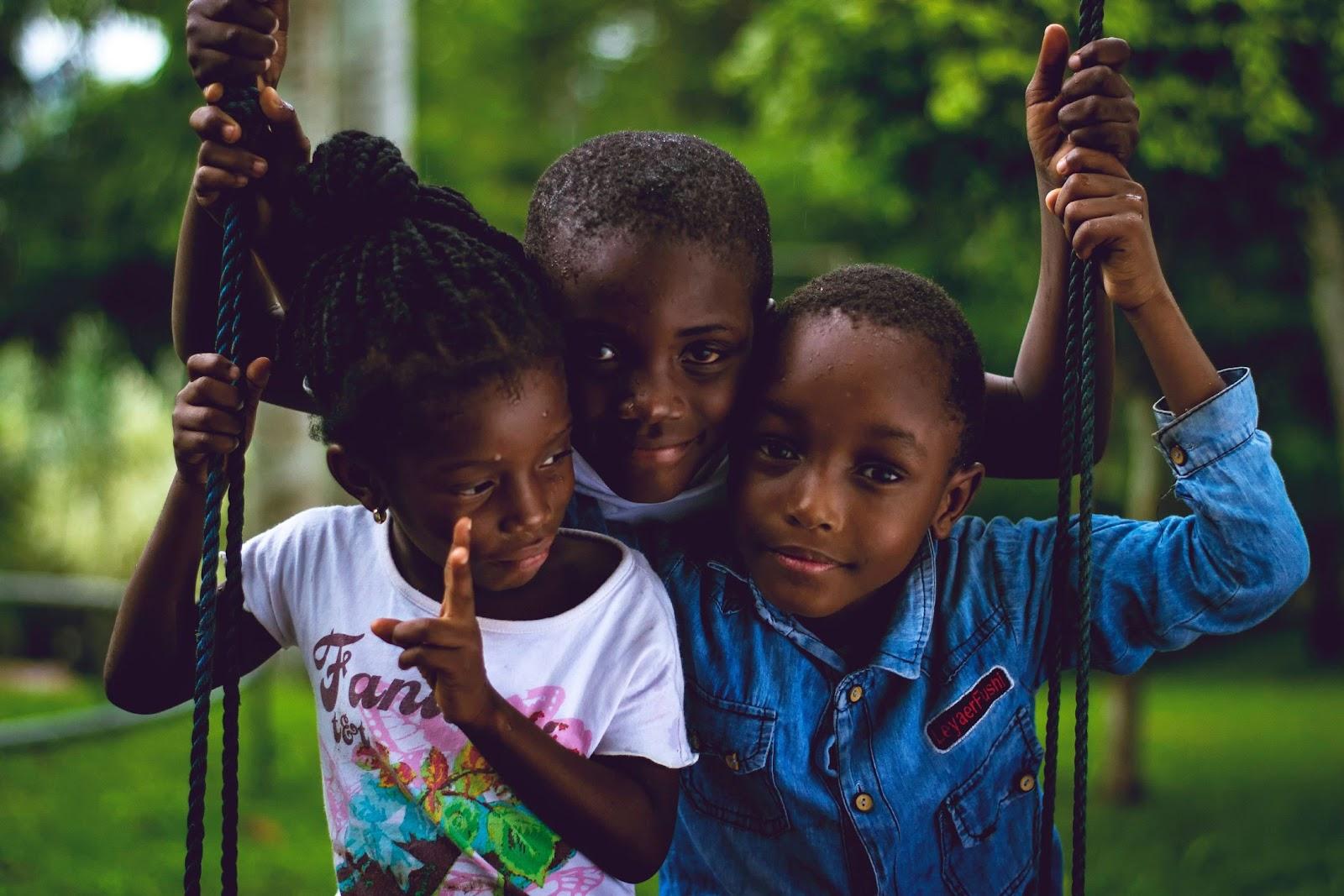 Photo of three children on a swing.