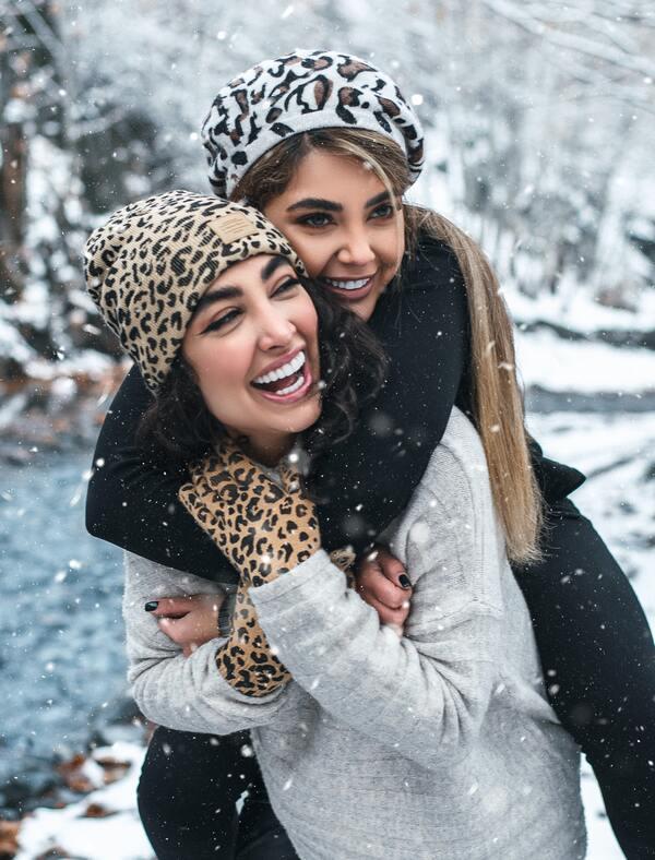 Duas amigas na neve, uma está em cima da outra e abraçando