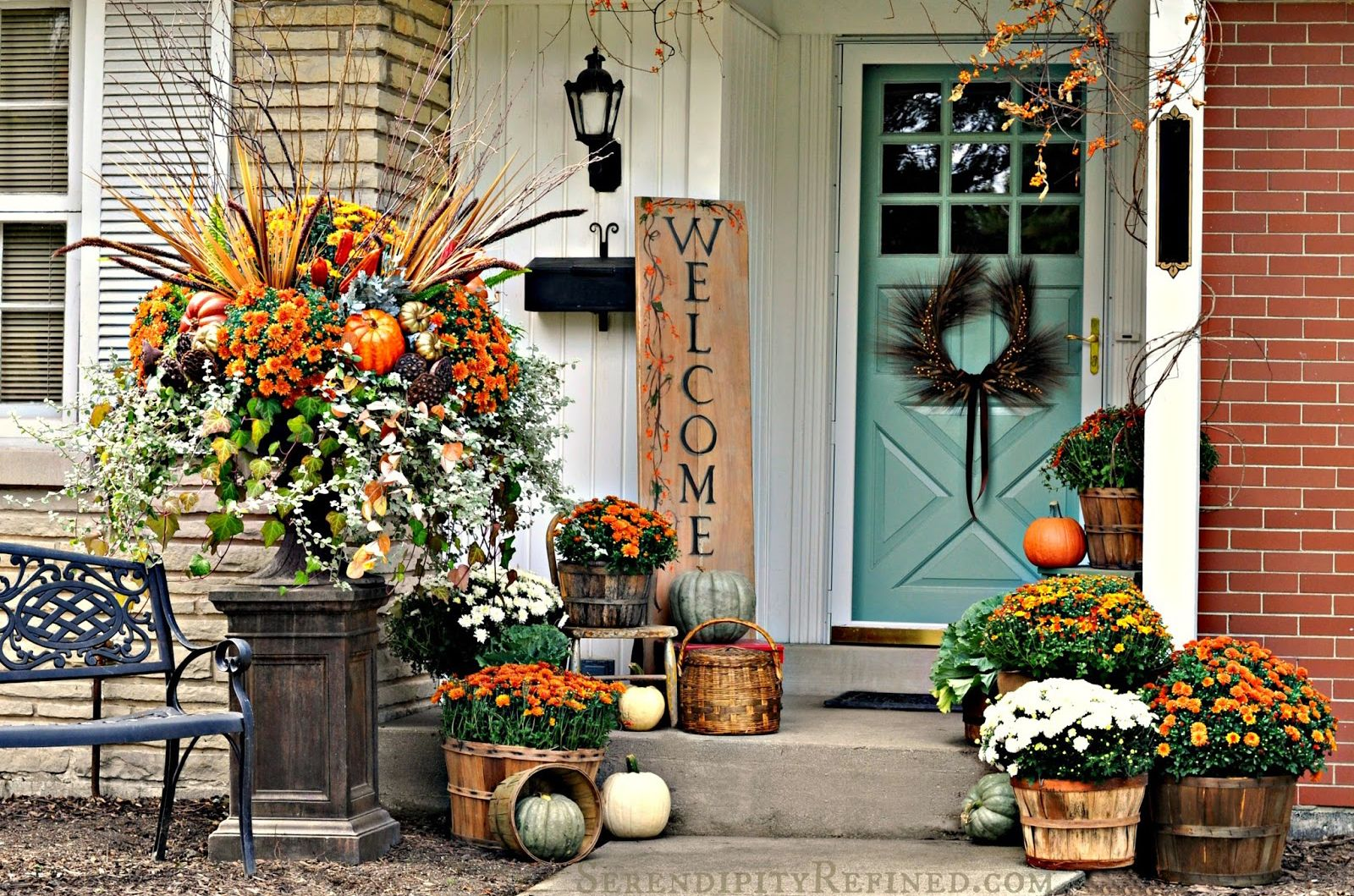 Porch decorated for the fall with orange and white mum flowers pumpkins and a welcome sign.