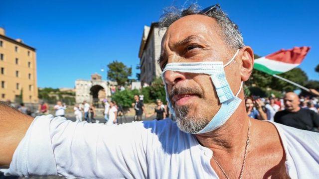 Мужчина в порванной маске на акции протеста против антиковидных ограничений в Риме, сентябрь 2020 года