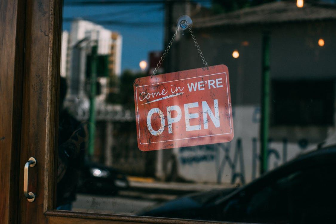 Open Signage Hanging on Glass Door of Vicinity