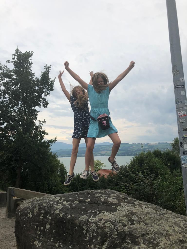 Zwei Mädchen stehen auf einem Stein und springen hoch
