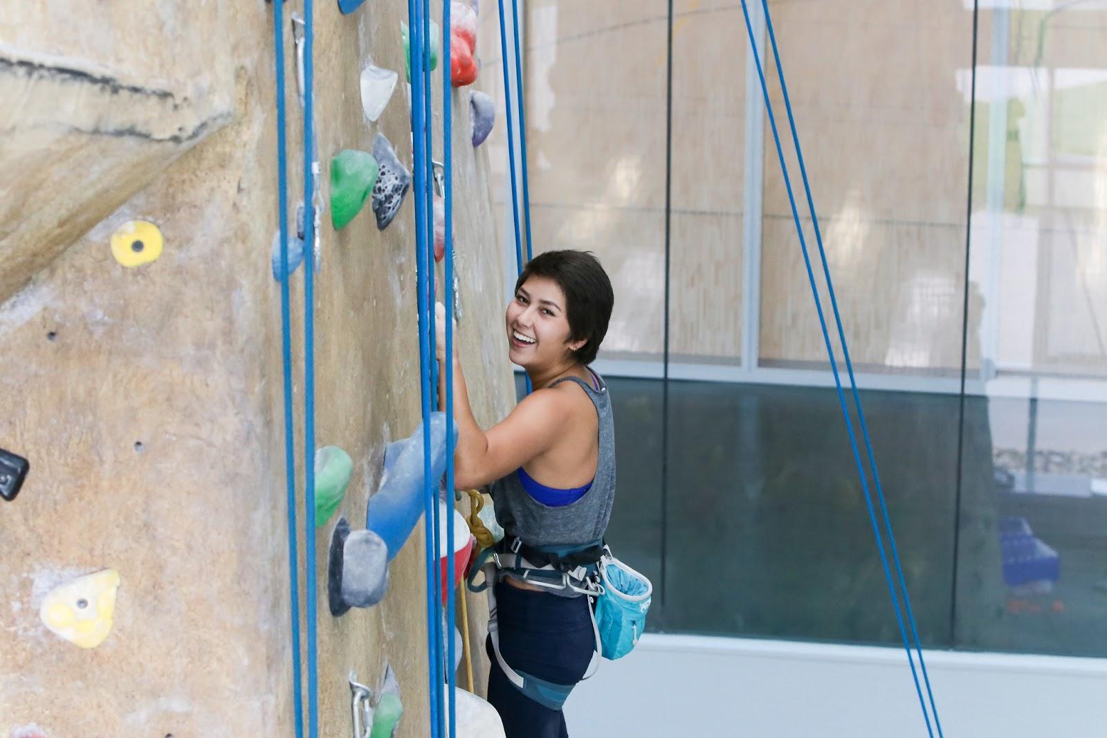 Photo of Christina climbing the BRIC's Bronco Peak and smiling.