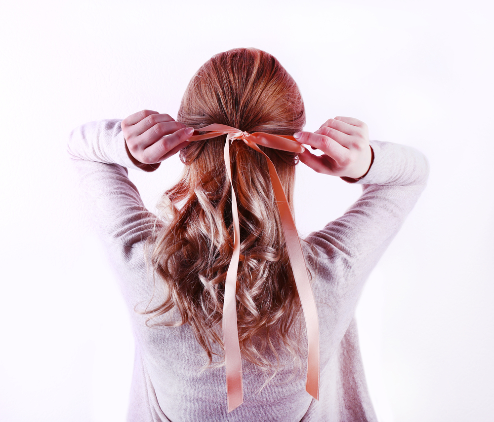 a woman ties back half of her red, curled hair with a ribbon tied into a large bow