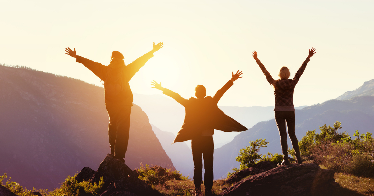 3 friends raising their hands on a mountain while watching the sunset