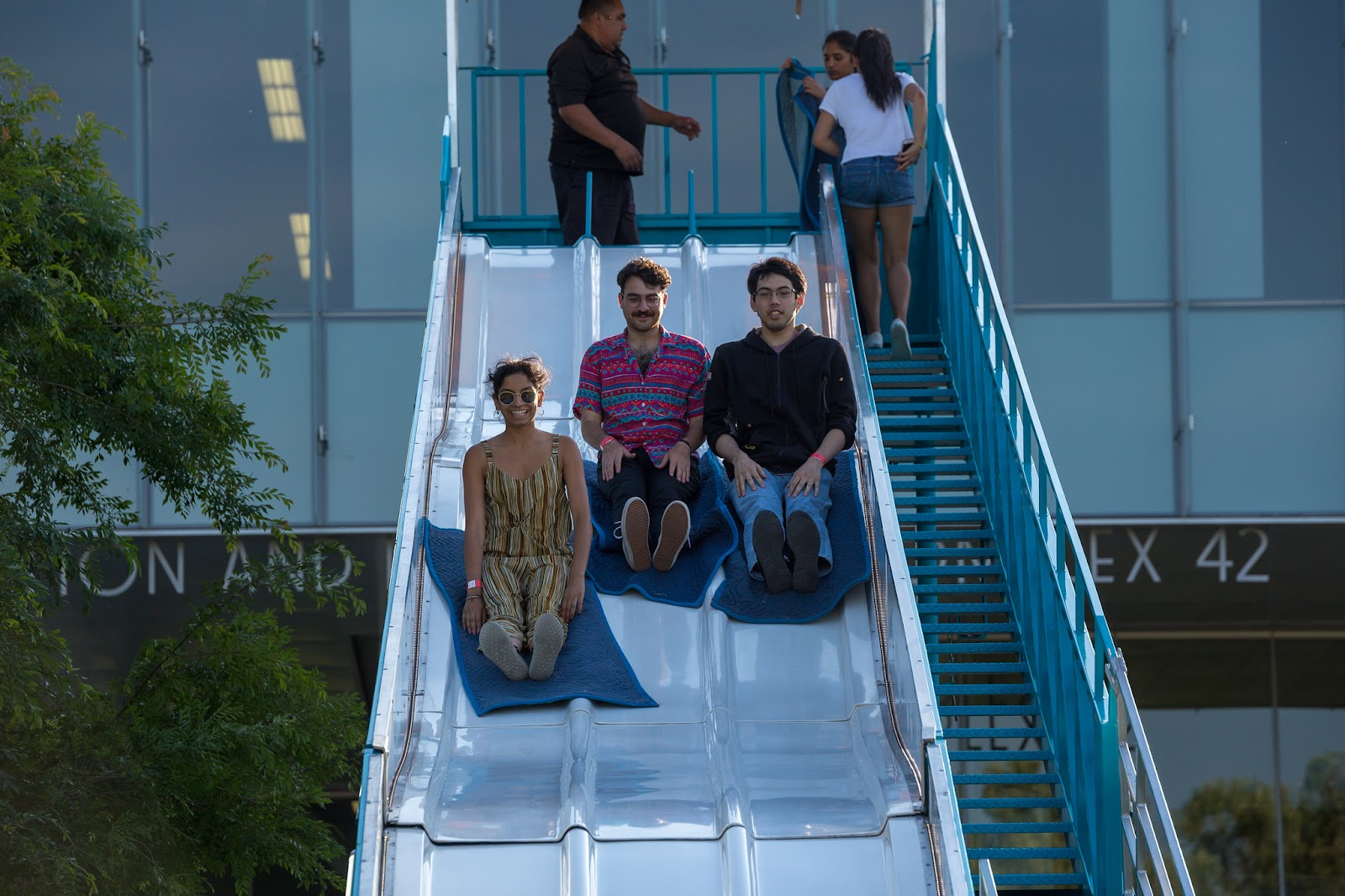 Three students race down the giant slide to see who will reach the bottom first