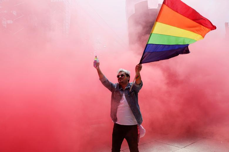 A participant flutters a rainbow flag at the Angel of Independence monument although the Mexican LGBT community called for an online gay pride celebration as a protective measure amid the coronavirus outbreak, in Mexico City, Mexico June 27, 2020. REUTERS/Henry Romero