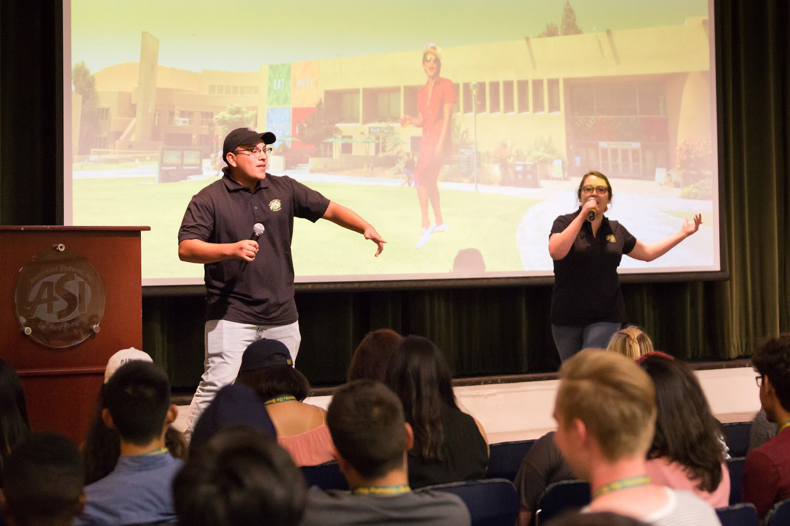 Chris Campos (left) and Sara Vasquez (right) on stage dancing during their ASI presentation to a crowd of freshman students.