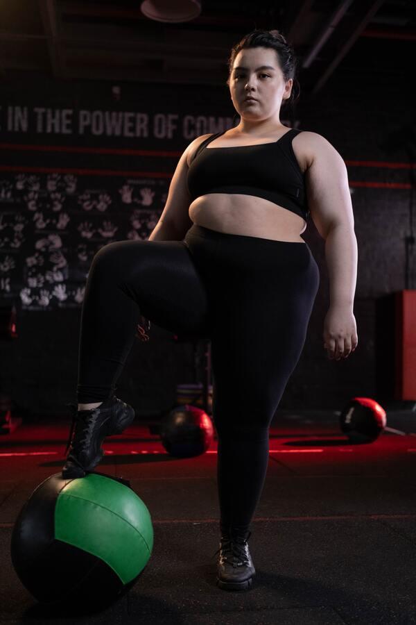 Foto de uma mulher plus size posando em uma academia com elementos para levantamento de pesos