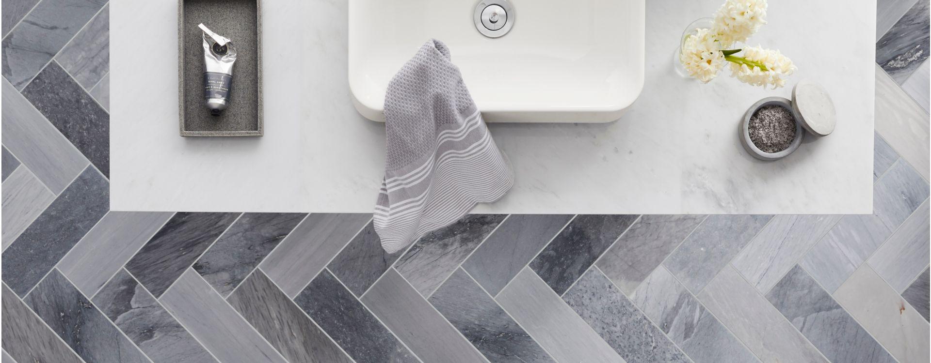 Gạch lát nền phòng tắm hình xương cá màu xám đậm.