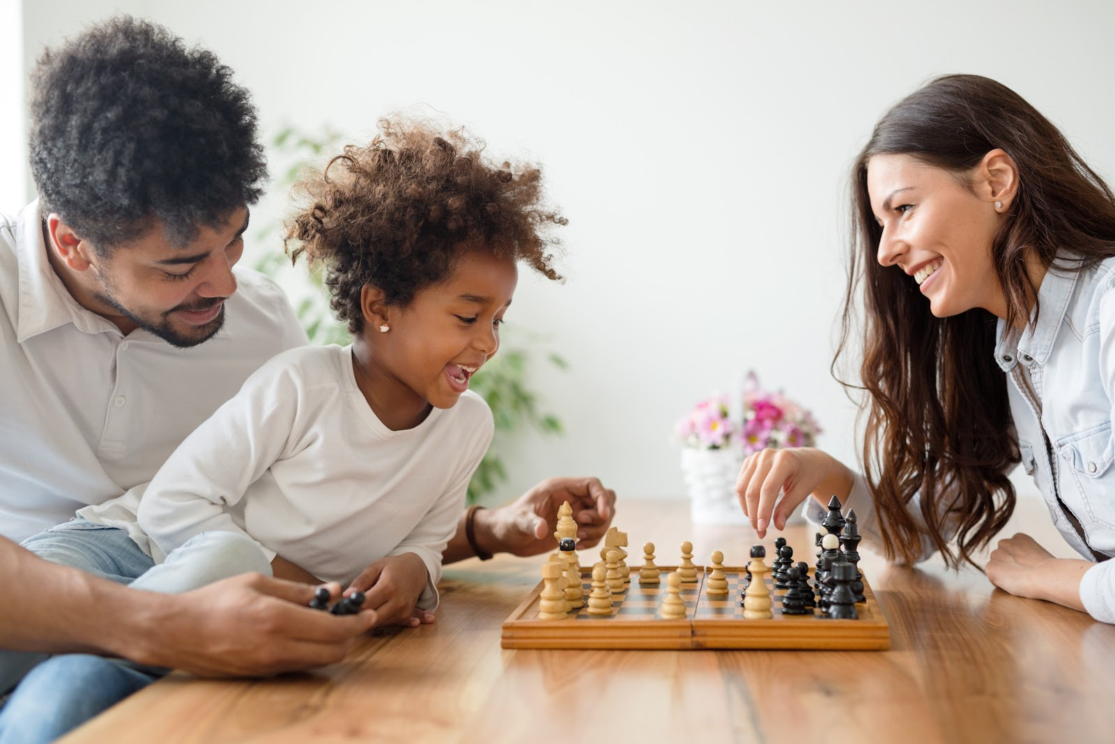 A mother and father play chess while their child watches.