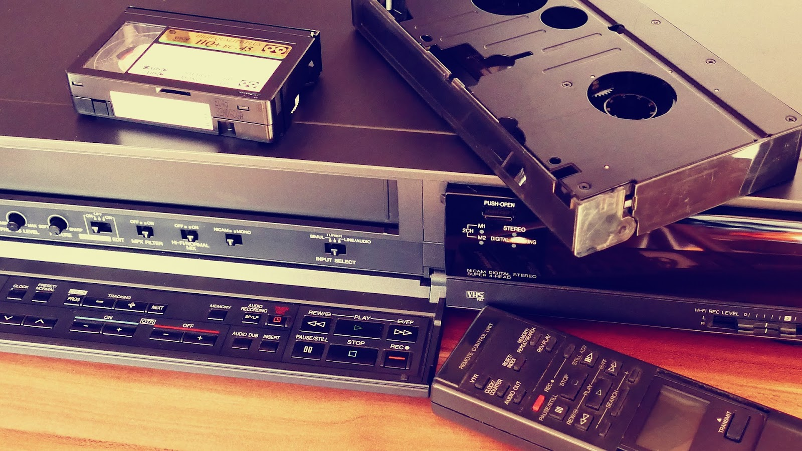 1990's technology: large and small video tapes, VCR, audio receiver, and remote