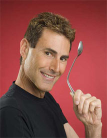 Uri Geller, a famous mentalist known for spoon bending, poses with a bent spoon.