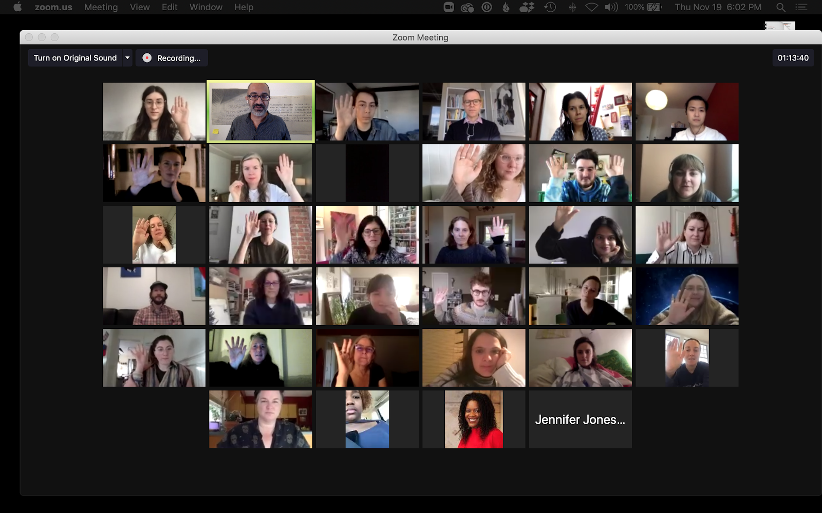 Screenshot of Zoom video conference with many people raising their hands