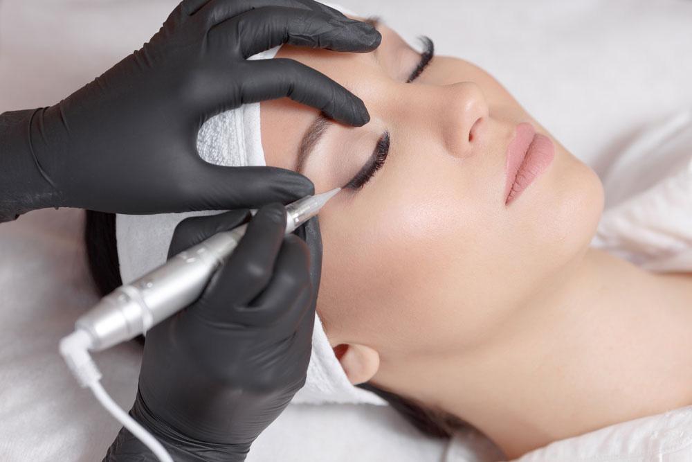 woman receiving permanent eyeliner tattoo procedure