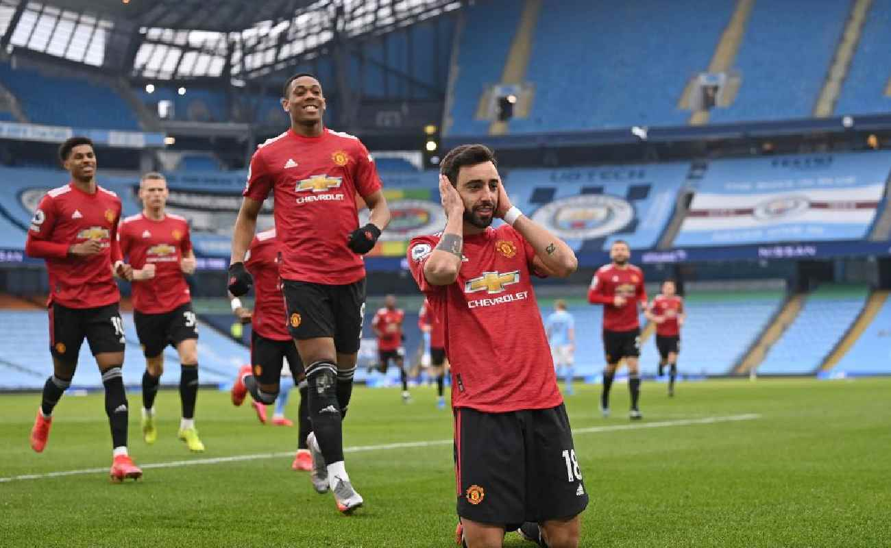 Alt: Bruno Fernandes covers his ears while celebrating scoring United's first goal against Manchester City - Photo by LAURENCE GRIFFITHS/POOL/AFP via Getty Images