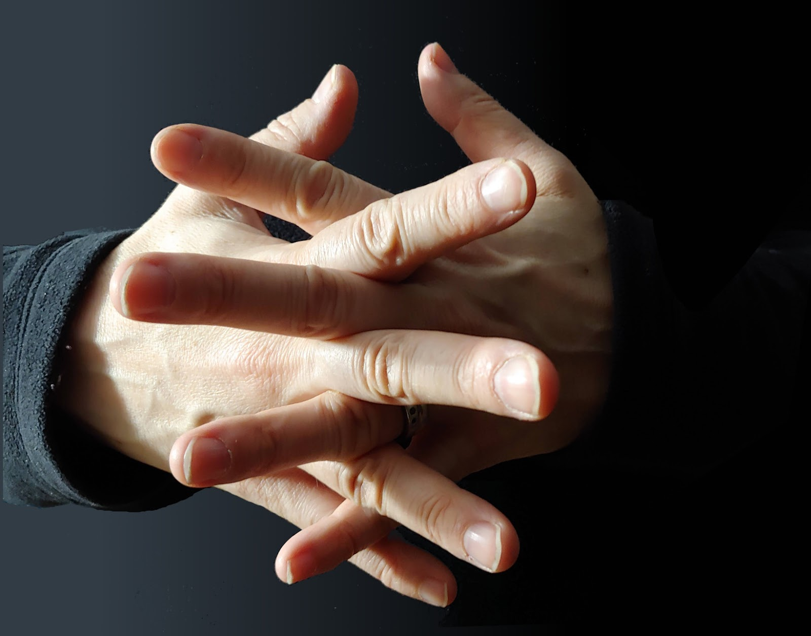 photo of hands with interleaved fingers