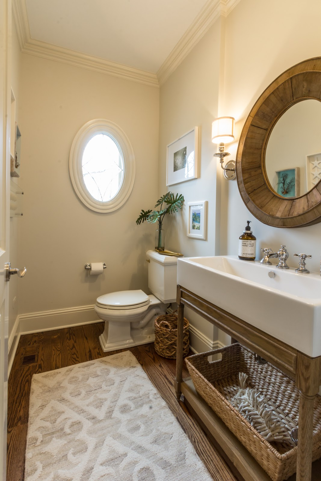 Powder room bath with apron sink and round mirror to match the round window. Wood and wicker adds texture and brings the natural world into the neutral, minimalist space.
