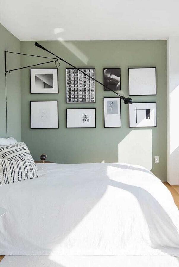 Quarto de casal com uma parede decorada com diversos quadros, as demais vazias e em tons claros com piso de madeira.