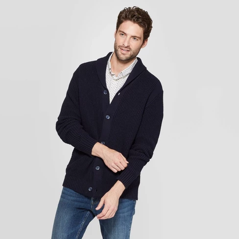 Individual posing while wearing a navy-blue cardigan over a patterned, collard shirt and jeans
