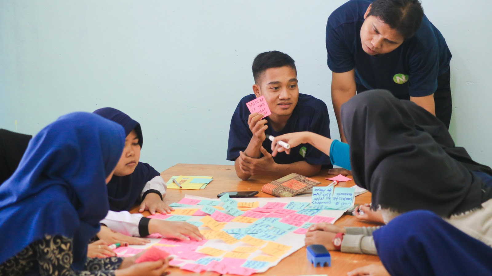 Two adults appear to be facilitating a group project discussion among four students.  There is a poster board covered with colored post-it notes in the center of the table.  The teacher is holding up one of the colored notes as he speaks with the students.