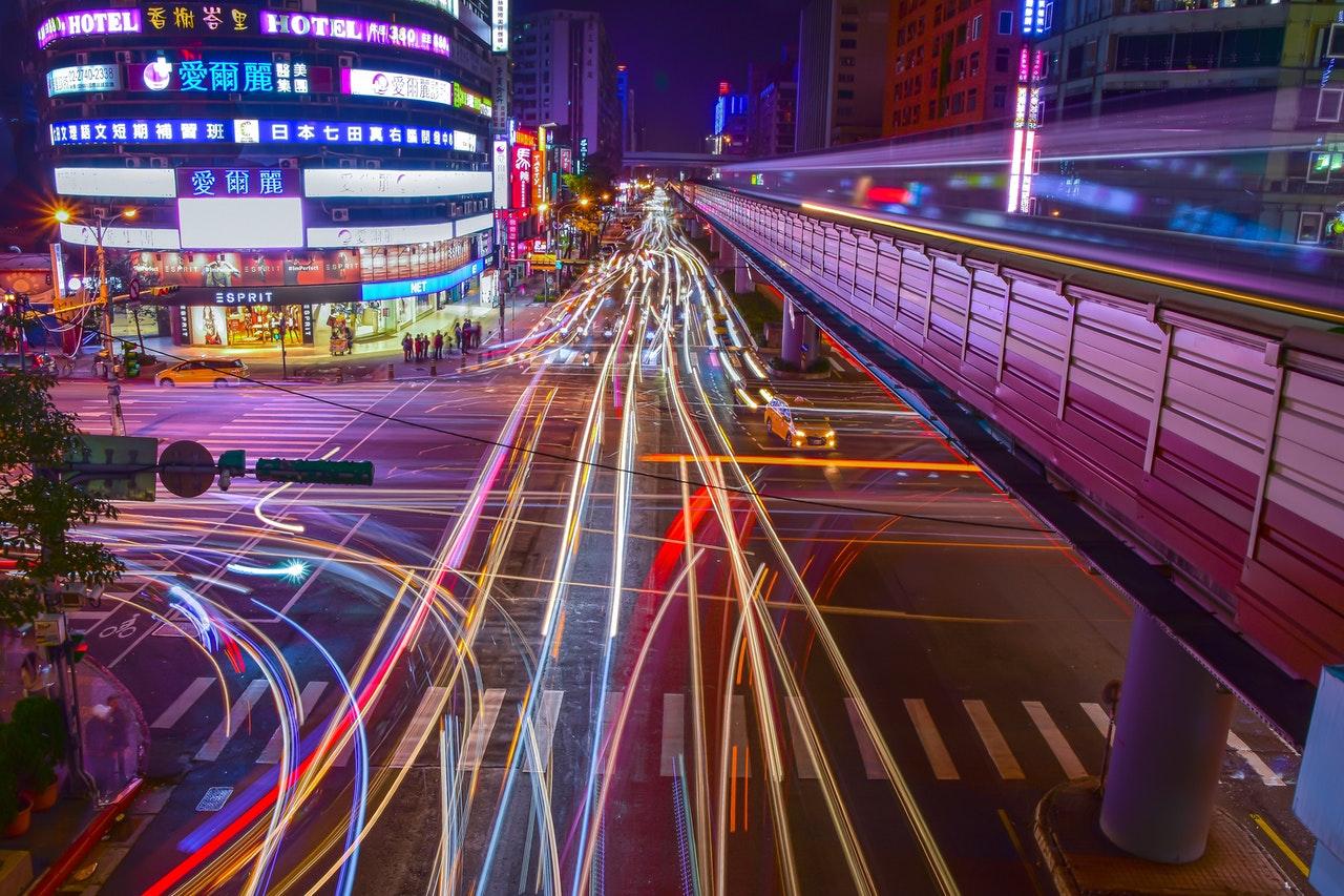 Światła drogowe nocą z efektem ciągnących się wiązek światła
