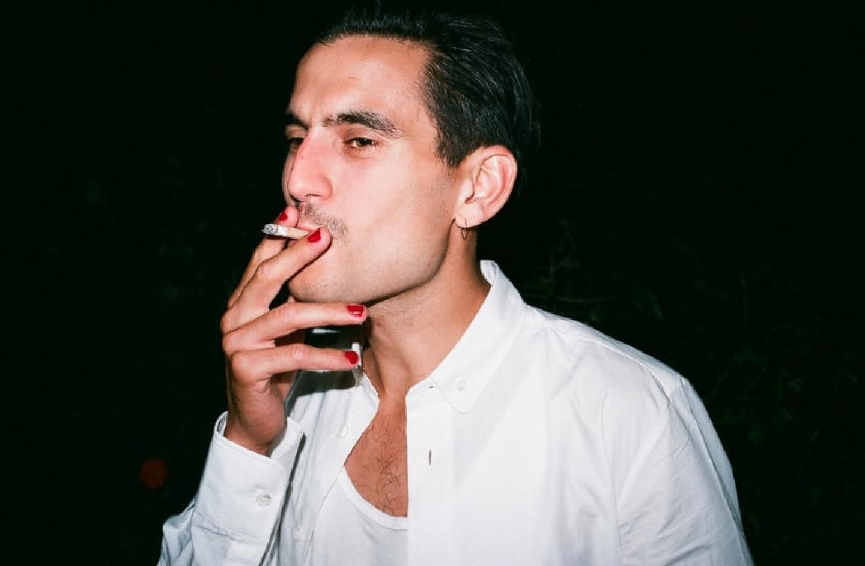 Photo d'un homme qui fume une cigarette et qui porte du vernis à ongles rouge