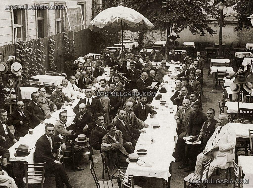 Група мъже, събрани на по халба бира в двора на бирария, 20-те години на ХХ век