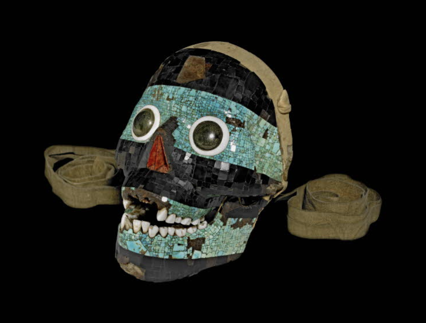 A photograph of a skull-like mask akin to the one above, crusted with gemstones in turquoise and black. The mask shows damage, with some teeth broken and places where the stones have fallen away.
