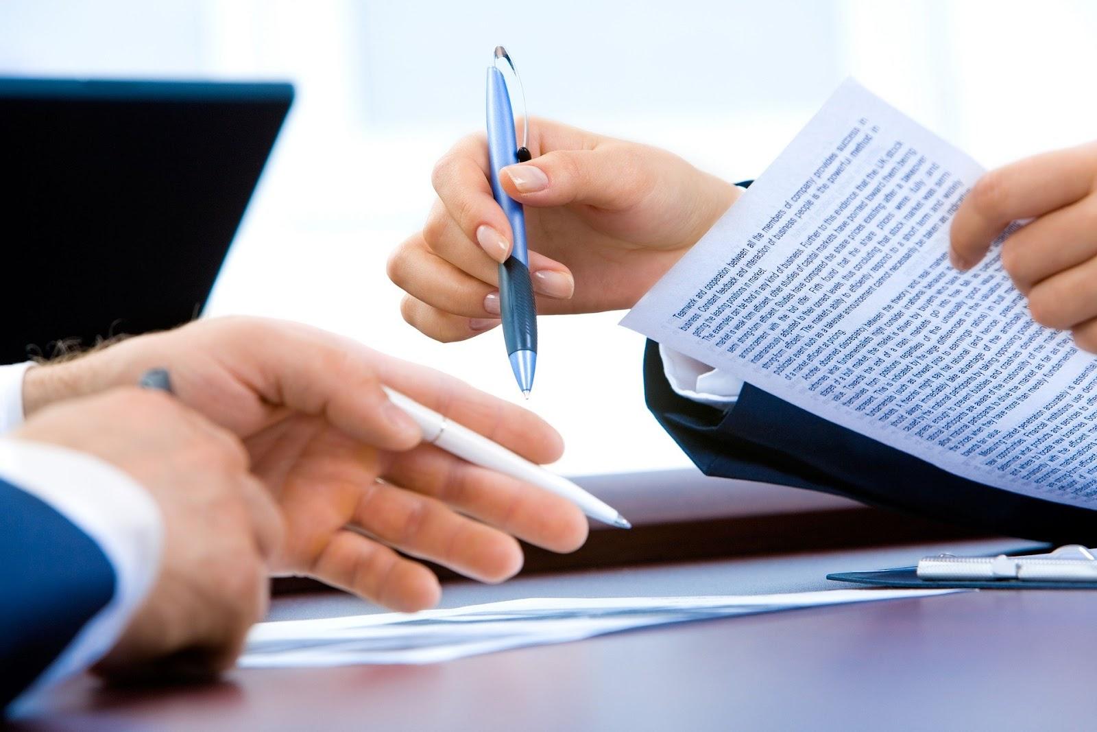 Na imagem temos a presença de dois pares de mãos sobre uma mesa. Ao fundo, temos um notebook de costas. O par de mãos a direita é feminino e está segurando um papel em uma mão e uma caneta azul em outra mão. À esquerda, temos o par de mão masculinos, uma mão está assinando um papel e a outra segura uma caneta branca.  A imagem tem como objetivo enfatizar a importância da Lei geral de proteção de dados durante transações presenciais.