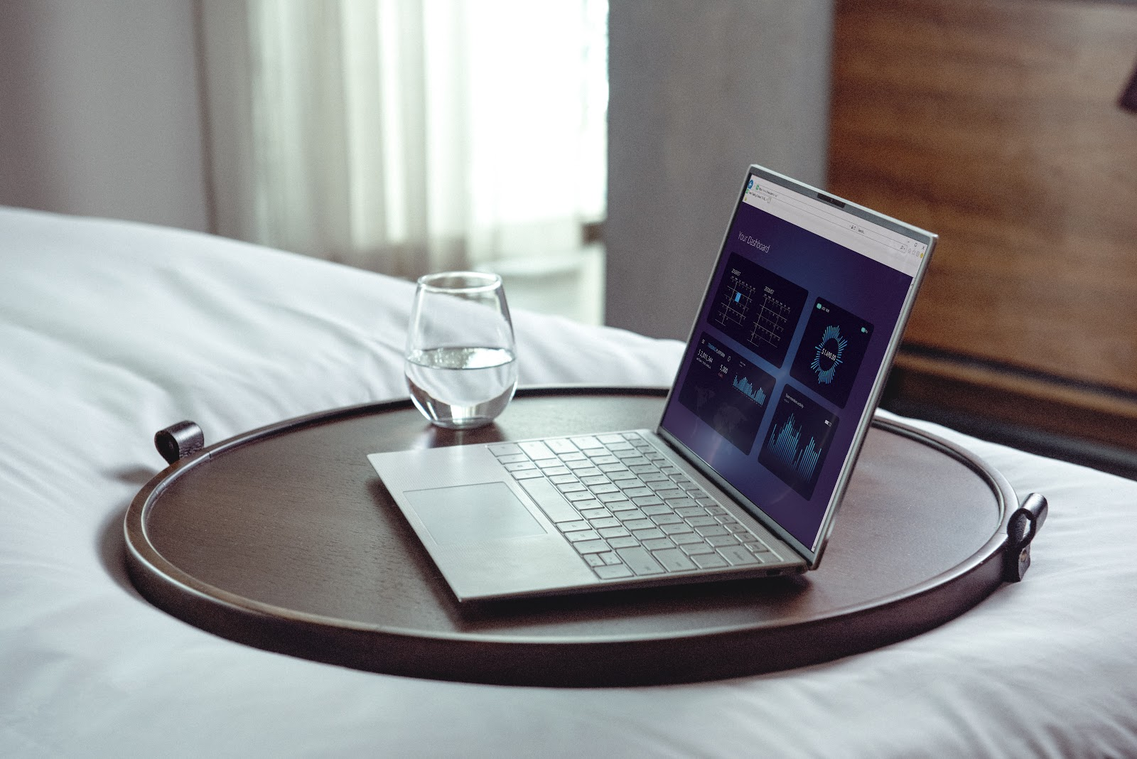 an open laptop on a tray next to a short glass of water