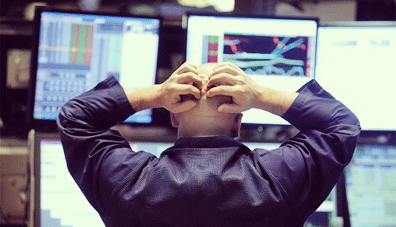 Homem com a mão na cabeça em frente ao computador.