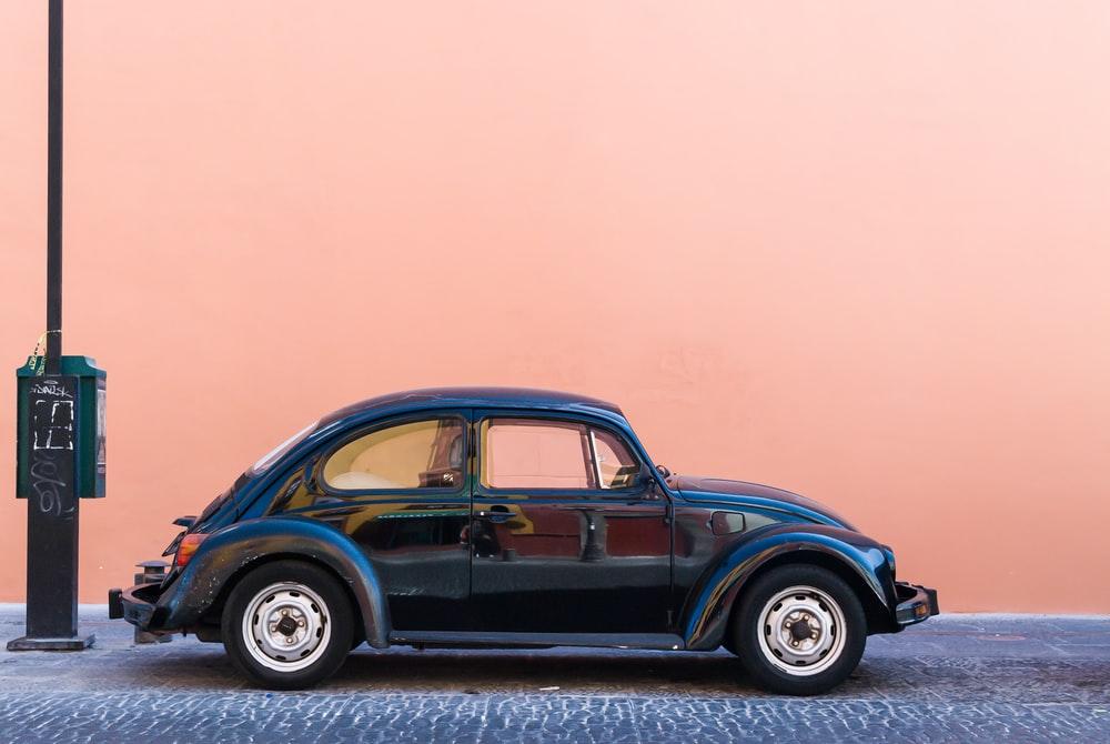 black Volkswagen Beetle beside beige wall