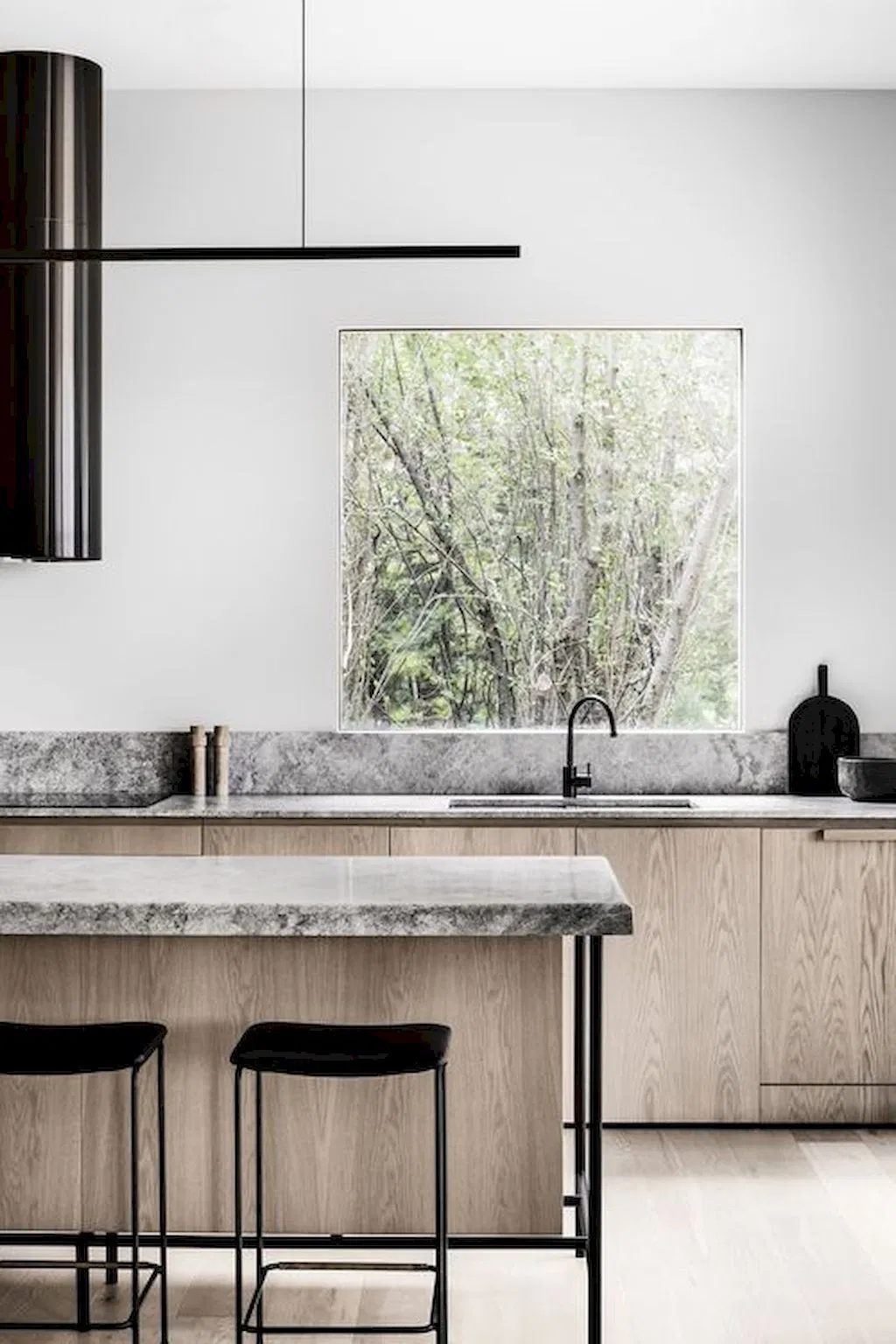neutral color minimalist kitchen with marble countertops and backsplash, black bar stools and large window