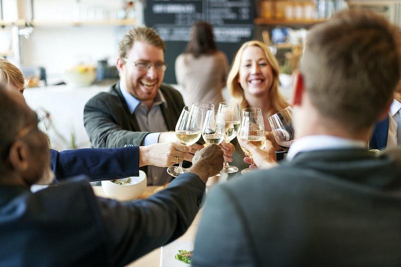 Várias pessoas brindando em uma mesa.