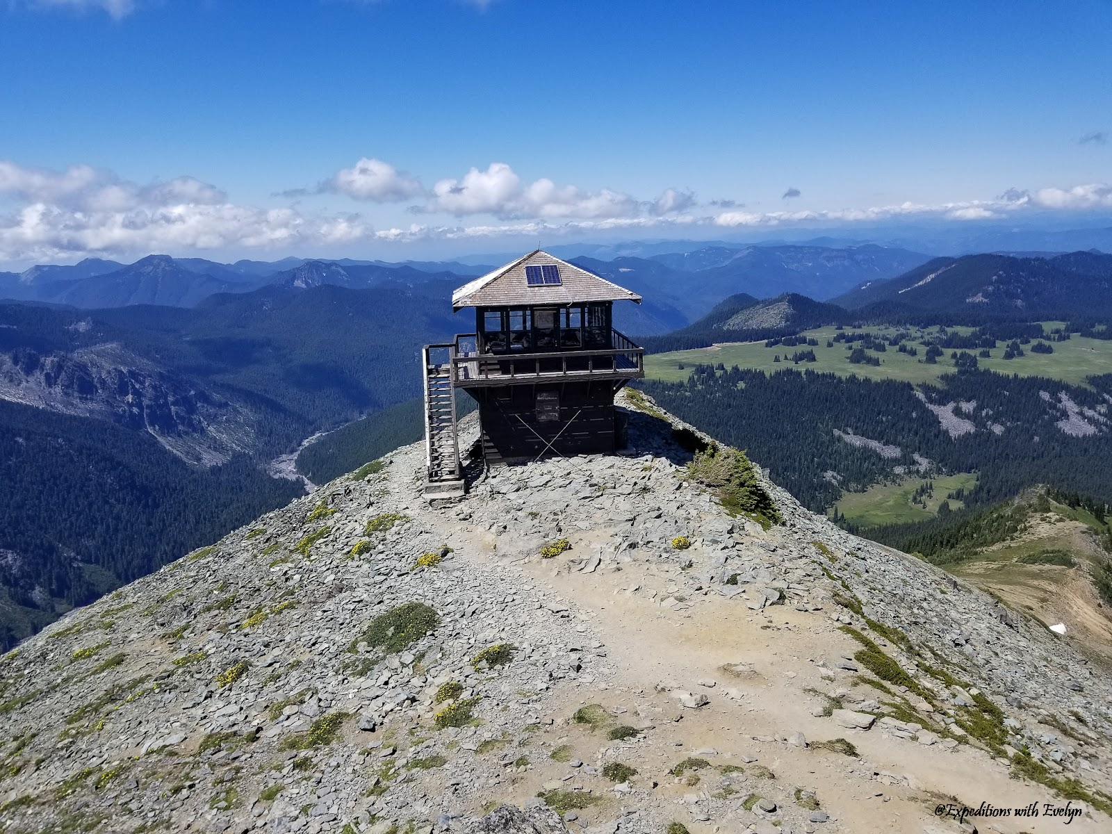 A fire lookout stands tall above lush green valleys below and mountains while clouds speckle the sky.