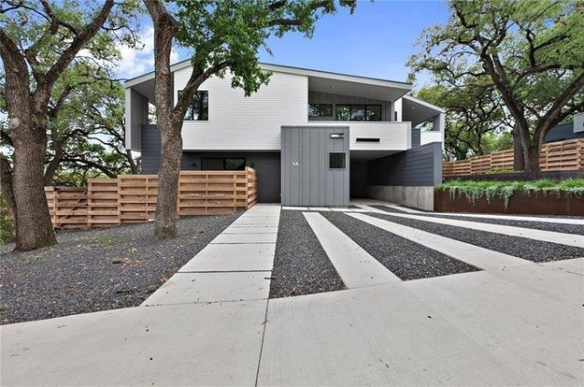 Two-story modern grey house with gravel driveway. Photo by Instagram user @nissiatxrealtor
