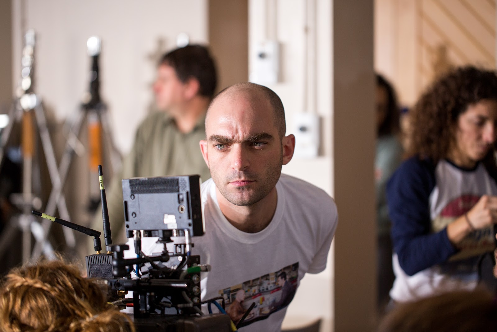 Image description: Samuel is white with blue eyes and a shaved head. Here he is wearing a casual white T-shirt and is looking into his camera viewfinder with a focused expression. Samuel is in the central foreground with several people behind him in blurred focus.
