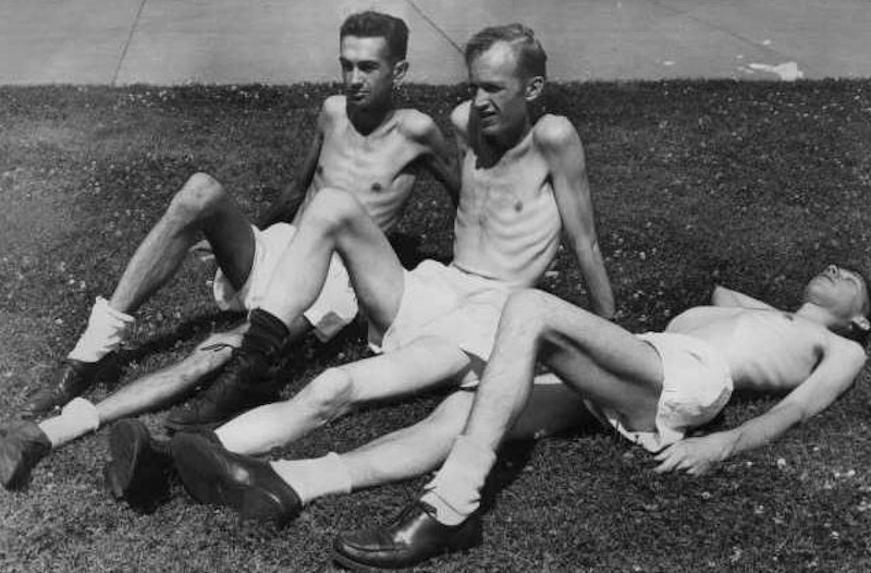 3 skinny males lying on the grass